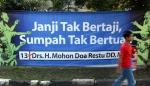 Seorang warga melintas di depan spanduk sebuah organisasi yang menyindir kampanye para caleg, di Jakarta, Senin (16/3).
